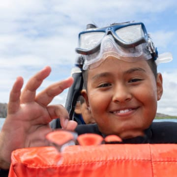 A Naveducando student indicates that he's enjoying learning how to swim with an OK sign and wide smile